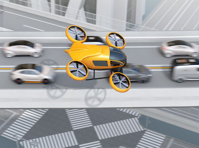 Yellow passenger drone flying over cars in heavy traffic jam