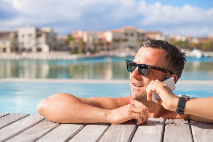 Man talking on phone while relaxing in the pool