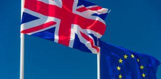 British flag and European flag waving against blue sky.