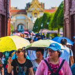 Un grupo de turistas chinos se protege del sol con paraguas.