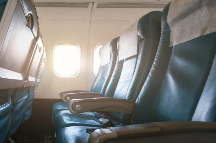 Interior of airplane with empty seats and sunlight .