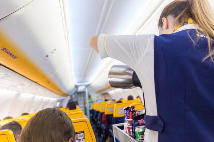 Stewardess serving passangers on Ryanair airplane flight .