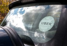 Rear window of a black Uber car with the white Uber sticker on the glass.