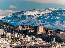 Vista de la Alhambra durante el invierno, montañas nevadas al fondo.