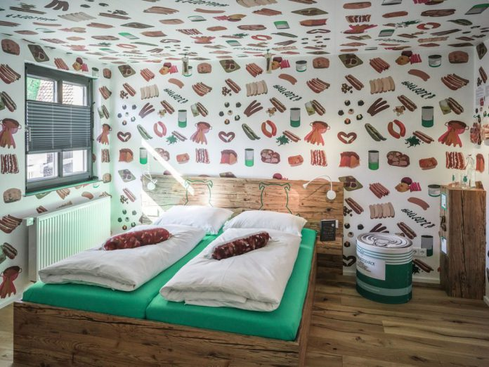 There are pictures of sausages on the wallpaper, sausage-shaped pillows on the beds and bratwurst hanging from the ceiling